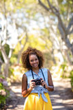 Smiling woman standing with digital camera Stock Image