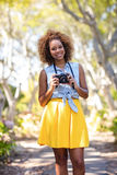 Smiling woman standing with digital camera Royalty Free Stock Image