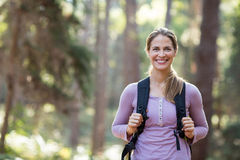 Smiling woman standing in forest carrying backpack. Portrait of smiling woman standing in forest carrying backpack Royalty Free Stock Photo