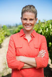 Smiling woman standing with hands on hip in vineyard Royalty Free Stock Images