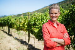 Smiling woman standing with hands on hip in vineyard Royalty Free Stock Photo