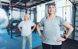Smiling woman standing with hands on hips at gym. Get up and move. Hazel eyed elderly lady posing into the camera with her hands on the hips while standing in a Stock Images