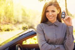 Smiling woman standing by her new car showing keys on a summer sunlit park background. royalty free stock photography