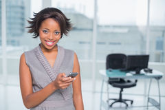 Smiling woman standing in her office and using her phone Royalty Free Stock Images