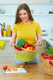 Smiling woman standing in kitchen holding basket with vegatables Stock Photos