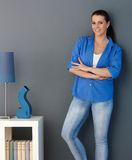Smiling woman standing at living room wall stock photos