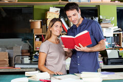 Smiling Woman Standing With Man In Paper Factory. Portrait of smiling women standing with men holding book in paper factory Royalty Free Stock Photography