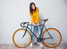 Smiling woman standing near bicycle Stock Images