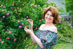 Smiling woman standing near blossoming dog rose Stock Photos