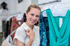 Smiling woman standing next to clothes rail Stock Photo