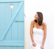 Smiling woman standing next to heart shape window shutter Royalty Free Stock Photo