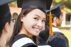 Smiling woman standing out from a graduation group. Smiling women standing out from a graduation group at campus Royalty Free Stock Photos