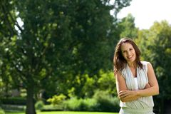 Smiling woman standing outdoors with arms crossed Stock Photo