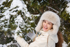 Smiling woman standing outdoors and shaking snowy spruce branch Royalty Free Stock Photo
