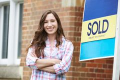 Smiling Woman Standing Outside New Home With Sold Sign stock photography