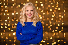 Smiling woman standing over holidays lights background Royalty Free Stock Photos
