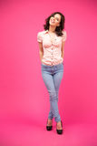 Smiling woman standing over pink background Royalty Free Stock Photo