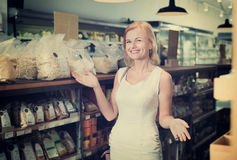 Smiling  woman standing among shelves Royalty Free Stock Photography