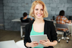 Smiling woman standing with tablet computer Stock Photo