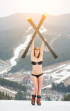 Smiling woman is standing on the top of slope and holding skis above head. Wearing swimsuit, boots, sunglasses Royalty Free Stock Photography