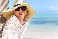 Smiling woman standing under palm tree Stock Photos