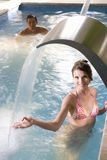 Smiling woman standing under swimming pool fountain. Smiling women standing under swimming pool fountain Royalty Free Stock Photo