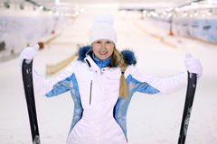 Smiling woman stands and keeps skis Stock Photos