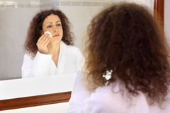 Smiling woman stands near mirror Royalty Free Stock Image