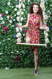 Smiling woman stands next swing overgrown with flowers. Next to green hedge with flowers Royalty Free Stock Photography