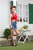Smiling woman stands next to table near house. With windows with shutters Stock Photos