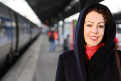 Smiling woman stands on railway platform Stock Photography
