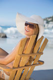 Smiling woman in straw hat relaxing in deck chair on the beach Stock Photo