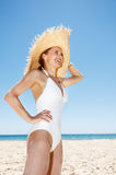 Smiling woman in straw hat at sandy beach looking into distance Stock Photography
