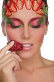Smiling woman with strawberries on face and hand Stock Photo