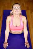 Smiling woman stretching back on mat in gym Stock Photos