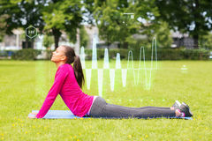 Smiling woman stretching back on mat outdoors Royalty Free Stock Images