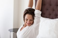 Smiling woman stretching on bed enjoying waking up happy concept. Smiling young woman stretching on cozy comfortable hotel bed in luxury bedroom enjoying good royalty free stock photos