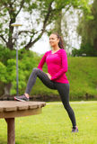 Smiling woman stretching on bench outdoors Royalty Free Stock Images