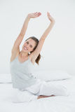 Smiling woman stretching her arms up in bed Royalty Free Stock Photography