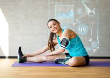 Smiling woman stretching leg on mat in gym. Fitness, sport, training, future technology and lifestyle concept - smiling woman stretching leg on mat in gym over Royalty Free Stock Photo