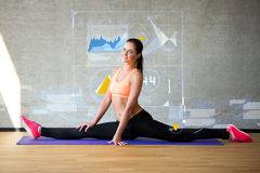 Smiling woman stretching leg on mat in gym Stock Image