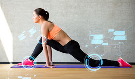 Smiling woman stretching leg on mat in gym Royalty Free Stock Photo