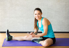 Smiling woman stretching leg on mat in gym Stock Photo