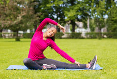Smiling woman stretching leg on mat outdoors Royalty Free Stock Images