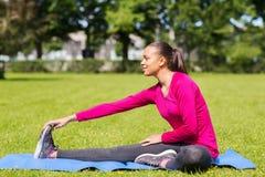 Smiling woman stretching leg on mat outdoors Stock Photos