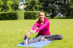 Smiling woman stretching leg on mat outdoors Royalty Free Stock Photo