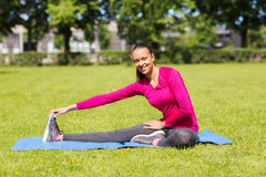 Smiling woman stretching leg on mat outdoors Stock Photo