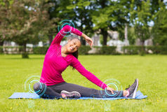 Smiling woman stretching leg on mat outdoors. Fitness, sport, training, park and lifestyle concept - smiling woman stretching leg on mat outdoors Royalty Free Stock Photos
