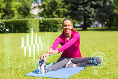 Smiling woman stretching leg on mat outdoors Royalty Free Stock Photos