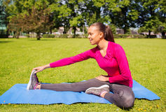 Smiling woman stretching leg on mat outdoors Stock Image